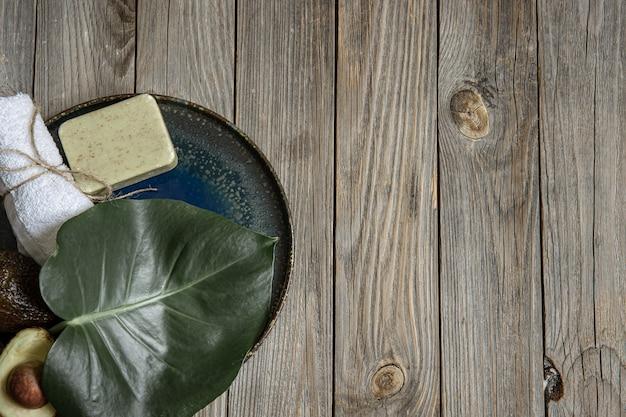 Composición de spa con jabón, aguacate, toalla y hojas en el espacio de copia de superficie de madera.