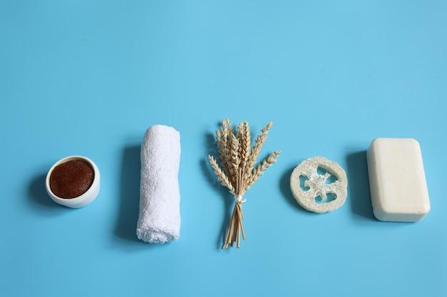 Composición de spa minimalista con jabón, esponja vegetal, exfoliante y toalla, concepto de higiene personal.
