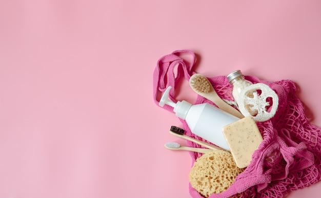 Composición de spa plana con artículos de higiene personal y accesorios de baño en una bolsa de hilo.