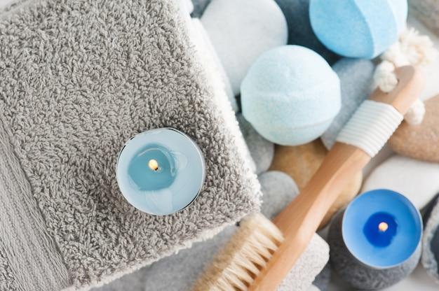 Composición de spa con toallas, velas encendidas, piedra pómez