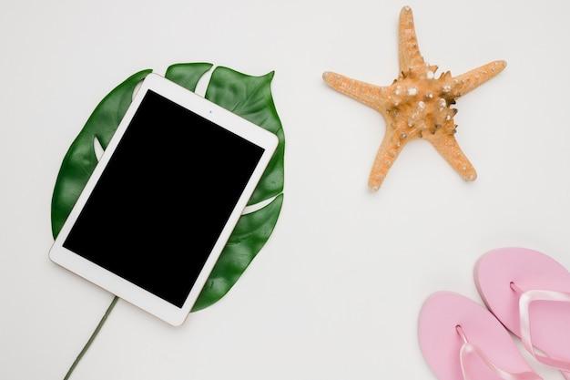 Composición de tabletas sandalias de mar y hoja de planta.