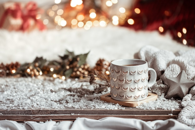 Composición con taza de navidad con bebida caliente en el espacio de copia de fondo abstracto borroso.