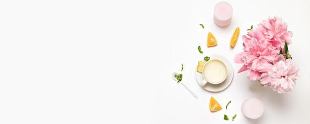 Composición con taza de té, flores de peone, naranja fresca, menta y azúcar.