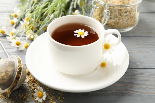 Composición con taza de té de manzanilla sobre fondo blanco de madera
