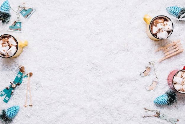 Composición de tazas cerca de juguetes navideños entre nieve