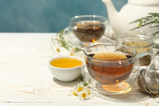 Composición con té de manzanilla en la mesa de madera blanca