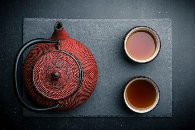 Composición de té con tazas de té de cerámica y tetera de hierro rojo.