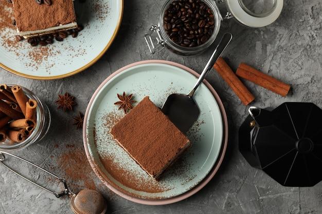 Composición con tiramisú, café y canela sobre mesa gris