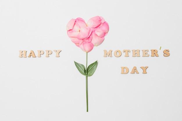 Composición del título feliz del día de las madres cerca de la floración rosa en forma de corazón