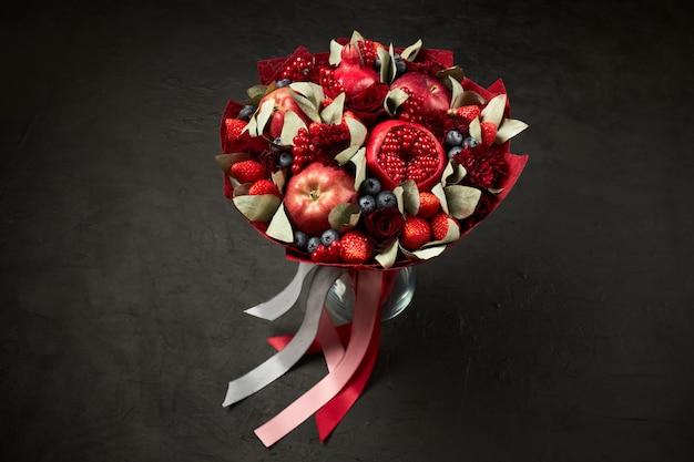 Composición única en forma de ramo de granadas, manzanas, fresas, grosellas rojas y rosas sobre un fondo negro.