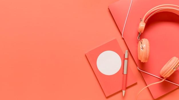 Composición de útiles escolares de color rosa y auriculares