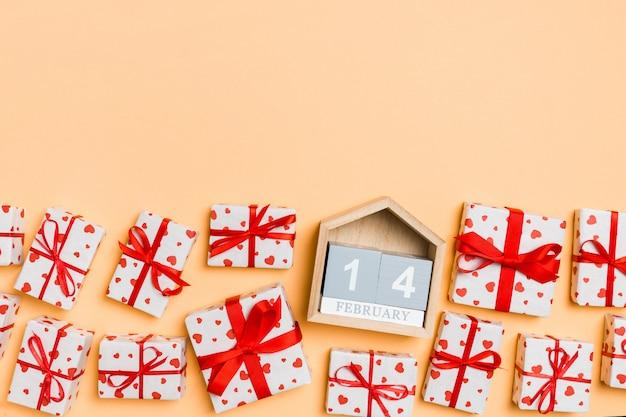 Composición de vacaciones de cajas de regalo con corazones rojos y calendario de madera sobre fondo colorido con espacio vacío para su diseño. el catorce de febrero. vista superior del concepto de san valentín