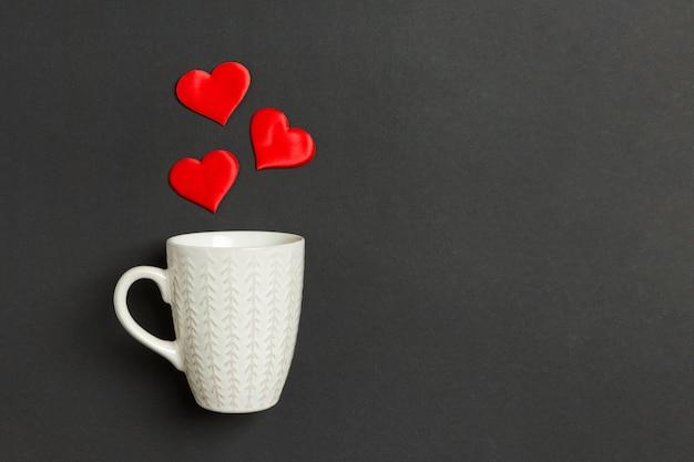 Composición de vacaciones de corazones rojos cayendo de una taza en la mesa. vista superior de saint