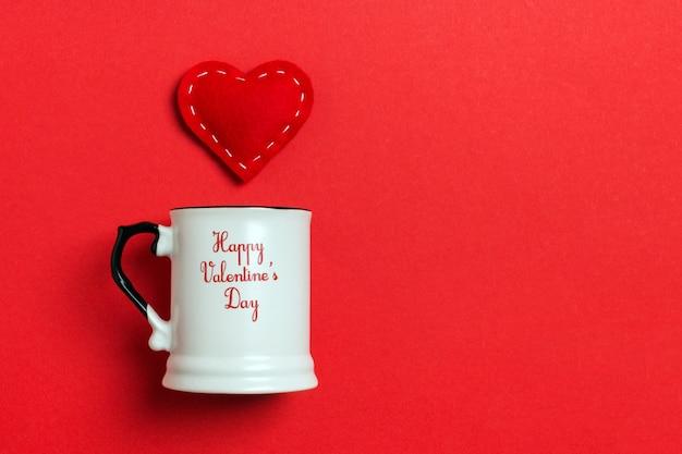 Composición de vacaciones de corazones rojos cayendo de una taza en la mesa.