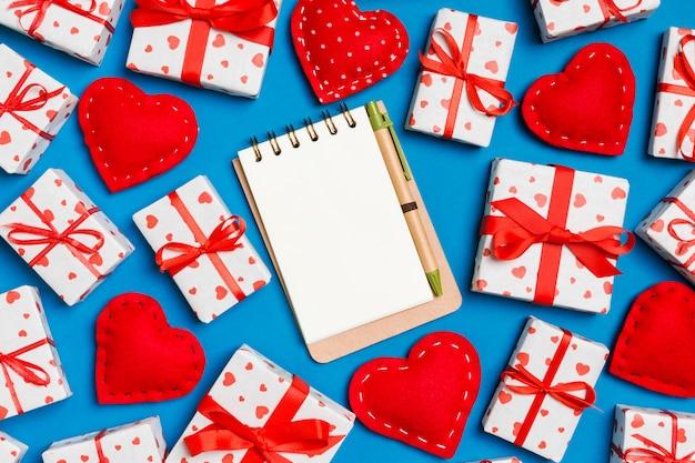 Composición de vacaciones de cuaderno, cajas de regalo y corazones textiles rojos sobre fondo colorido con espacio vacío para su diseño. vista superior del concepto de san valentín