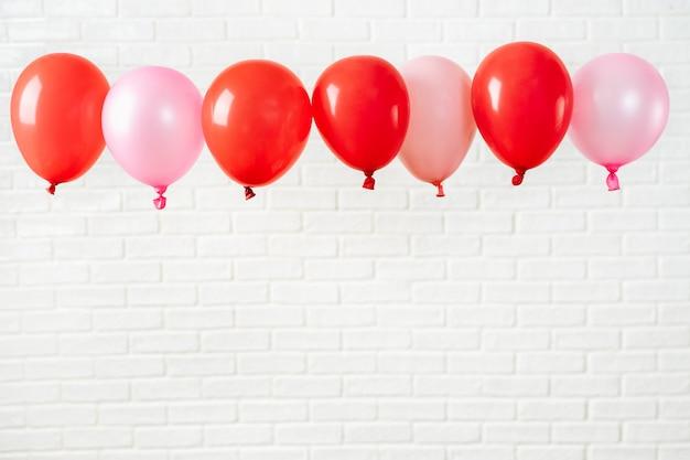 Composición de vacaciones con globos rojos sobre blanco