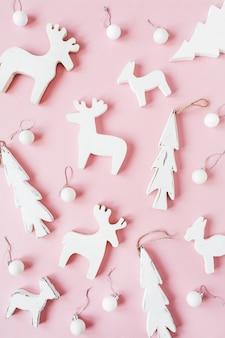Composición de vacaciones de navidad año nuevo. adornos navideños, ciervos de juguete, decoración de abeto en rosa