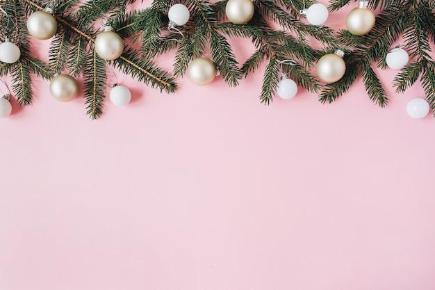 Composición de vacaciones de navidad año nuevo. ramas de agujas de abeto, bolas de adorno navideño en rosa