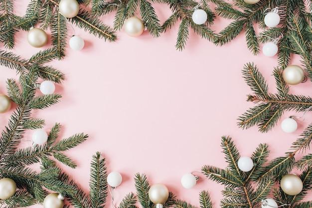 Composición de vacaciones de navidad año nuevo. simulacros de marco con espacio de copia en blanco, ramas de agujas de abeto, adornos navideños en rosa