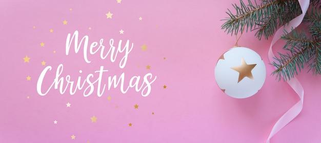 Composición de vacaciones de navidad en pared rosa con letras feliz navidad