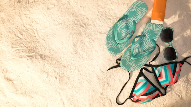 Composición de vacaciones de playa sobre fondo de arena