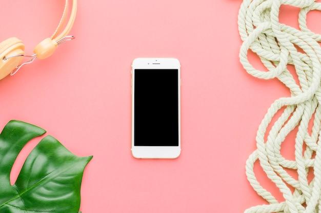 Composición de vacaciones de playa con teléfono móvil sobre fondo de color