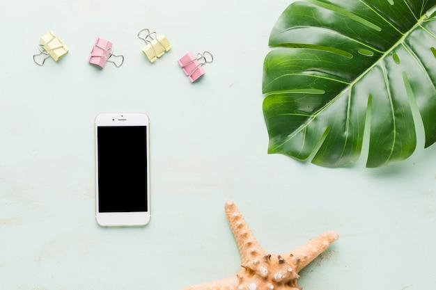 Composición de vacaciones de playa con teléfono sobre fondo claro