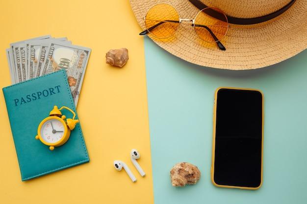 Composición de vacaciones de verano. gafas de sol, smartphone, sombrero y pasaporte con billetes de dinero