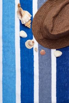 Una composición de vacaciones de verano en una toalla de playa con conchas marinas y un sombrero.