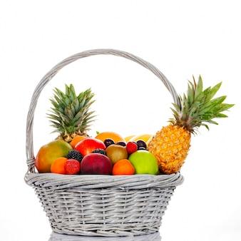 Composición con una variedad de frutas en canasta de mimbre sobre fondo blanco.