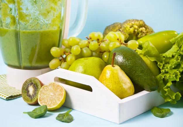 Composición con una variedad de vegetales verdes crudos orgánicos y friuts en la bandeja de madera blanca y licuadora.