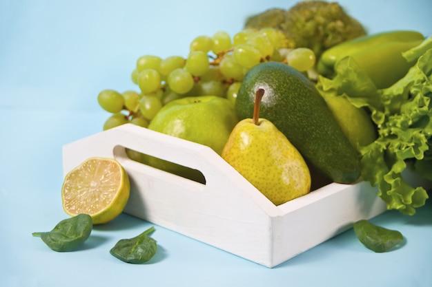 Composición con una variedad de vegetales verdes orgánicos crudos y friuts en la bandeja de madera blanca.