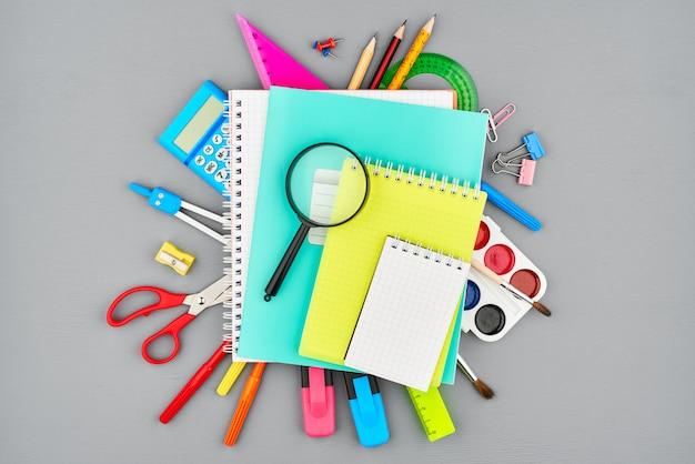 Composición de varios artículos de papelería y cuadernos en un pupitre gris