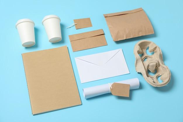 Composición con vasos de papel y material de oficina sobre fondo azul, espacio de copia