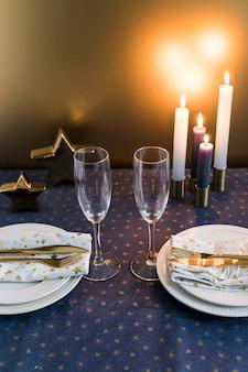 Composición de vasos, platos y cubiertos cerca de velas encendidas.