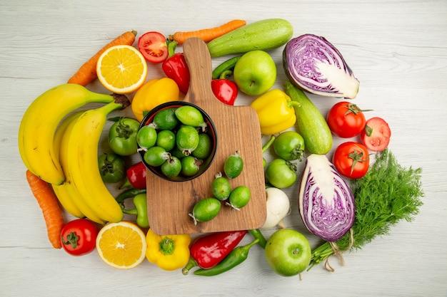 Composición vegetal vista superior con frutas sobre fondo blanco