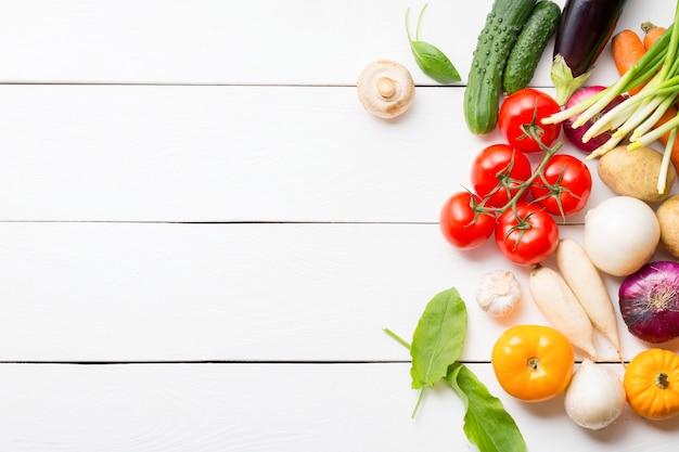 Composición de vegetales orgánicos saludables en mesa de madera blanca con espacio de copia.