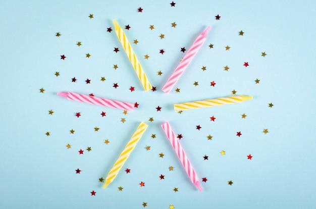Composición de velas de colores sobre fondo azul, decoración de fiesta y celebración.