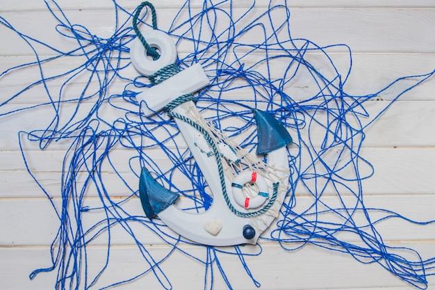 Composición veraniega con ancla y cuerda azul