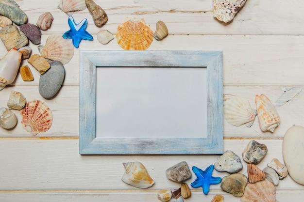 Composición veraniega con conchas marinas y marco en blanco
