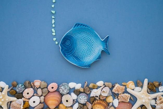 Composición veraniega con pez azul y variedad de conchas marinas