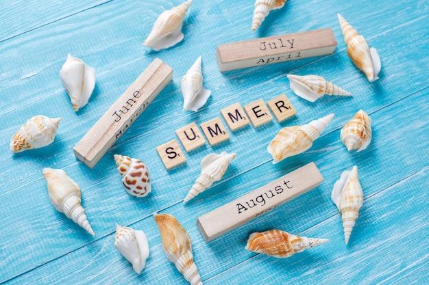 Composición de verano con conchas de mar y bloques de madera.