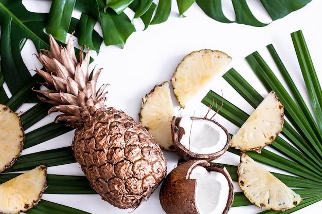 Composición de verano con hojas tropicales y frutas en blanco