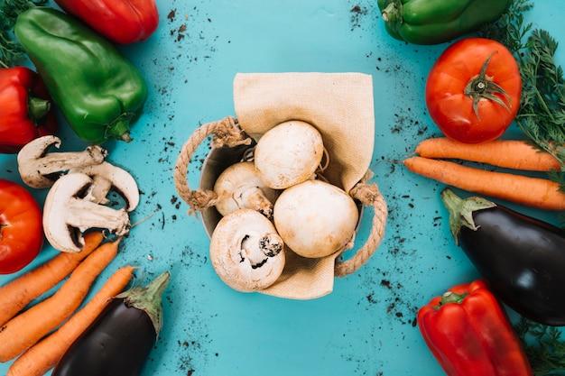 Composición de verduras con cesta de champiñones en medio