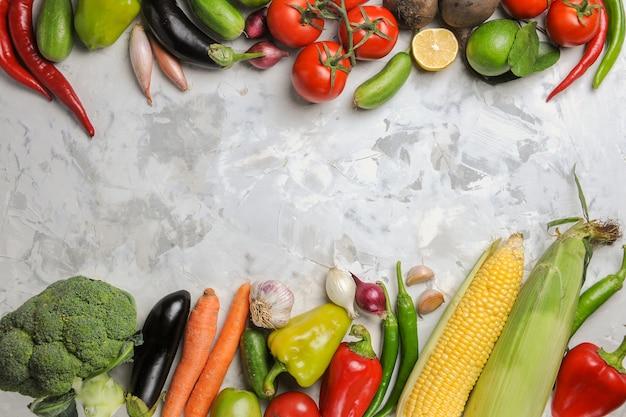Composición de verduras frescas de vista superior en piso blanco