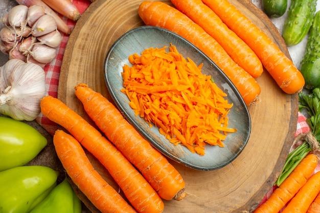Composición de verduras frescas de vista superior con zanahoria sobre fondo blanco
