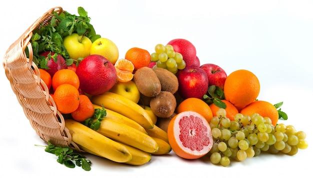 Composición con verduras y frutas en cesta de mimbre aislada