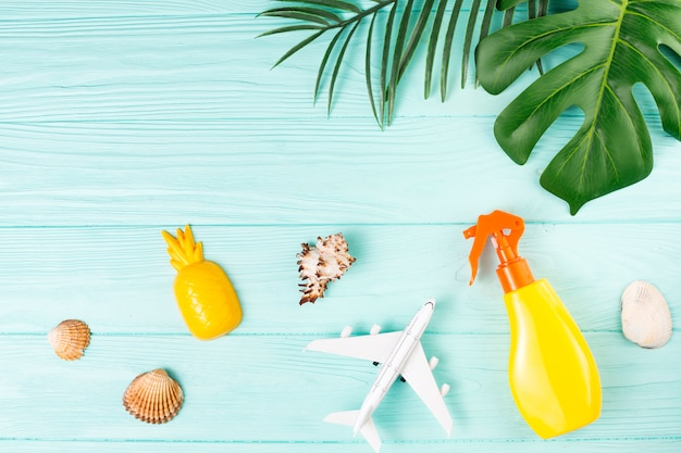 Composición de viajes exóticos con conchas, juguetes y hojas verdes.