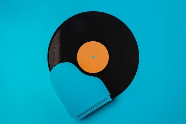 Composición de vinilo negro de vista superior con piano azul