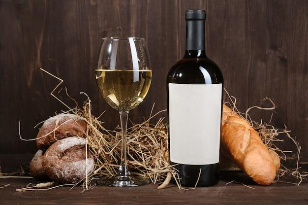 Composición de vino blanco con botella de pan y copa de vino en la mesa de madera